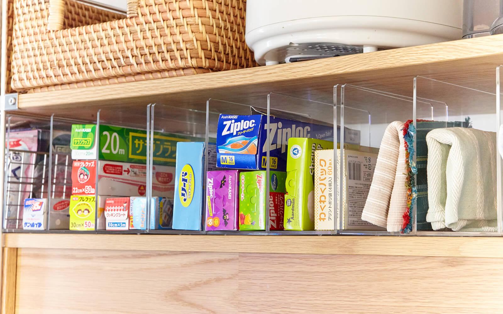 ラップやふきんなど、キッチンまわりの小物収納に、棚のすき間を活用。アクリル仕切りスタンドを使った、探しやすく取り出しやすい収納スペースです。