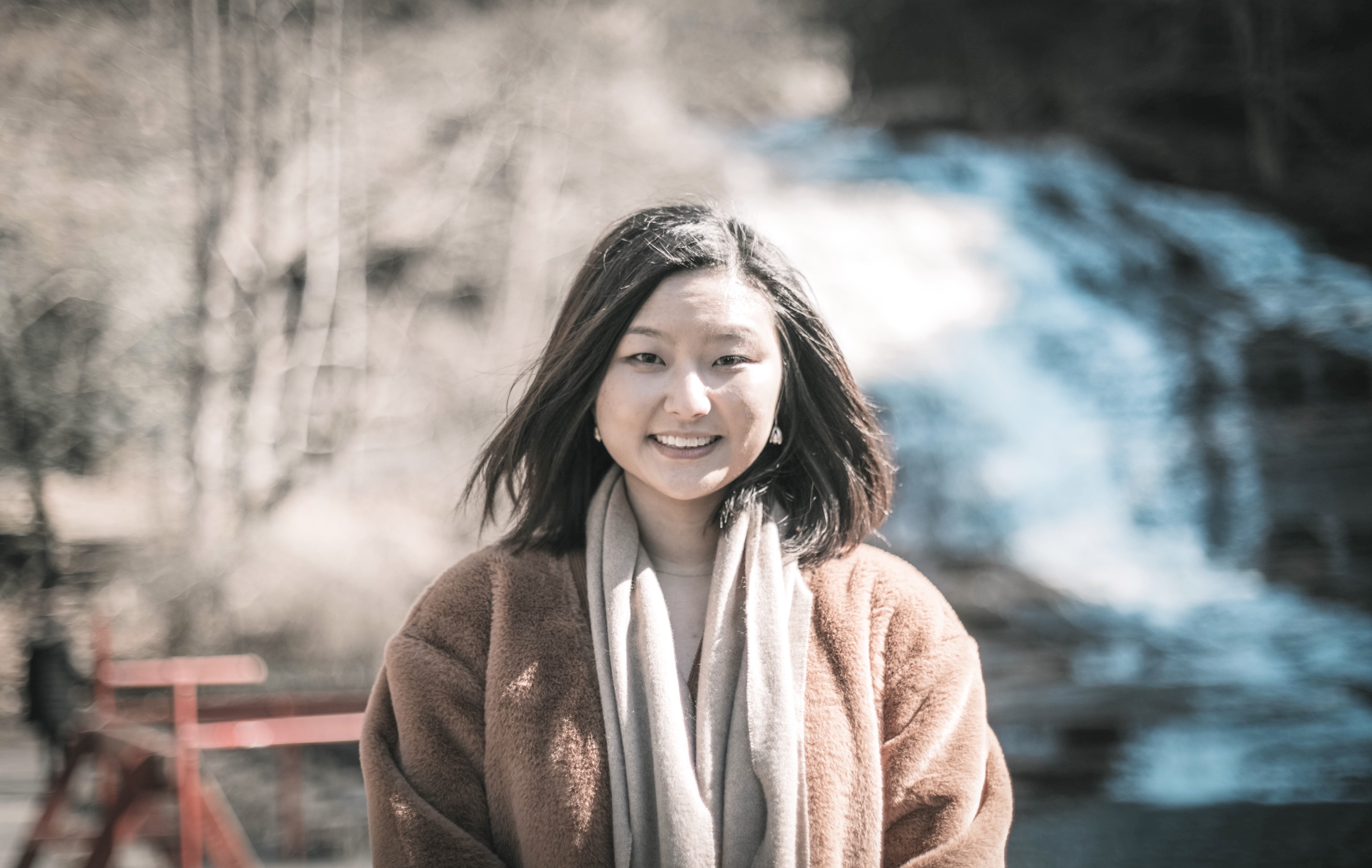 Hannah Cho, an Asian woman, is smiling. She is standing outside, in front of a tree and a hill of snow that is blurred and in the background.