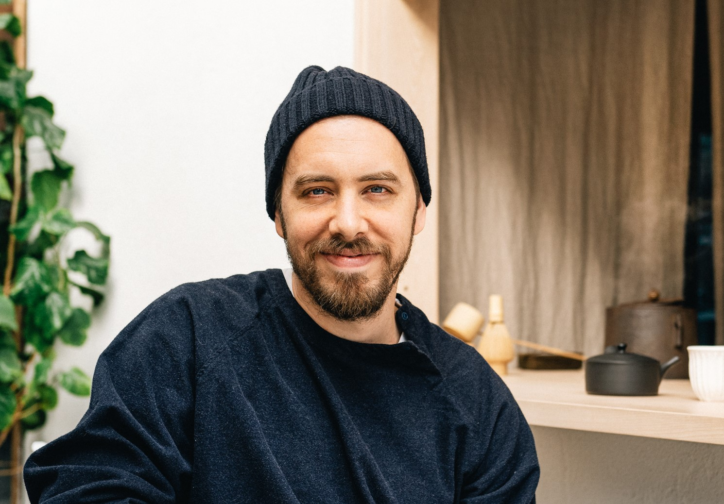 Caucasian male sits in a chair outdoors. He has brunette facial hair, and is wearing a black beanie and a black MUJI pullover shirt.